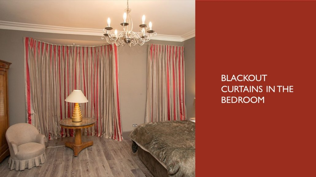 Cosy bedroom with fur gold and red accents with striped blackout curtains on a distinction pole
