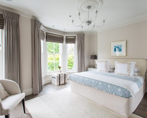 A large Master Bedroom with a full bay is treated sympathetically using unlined roman panels in Voile Melissa for daytime privacy couple with a lath & fascia for twin pleat blackout curtains in Luxor Natural.