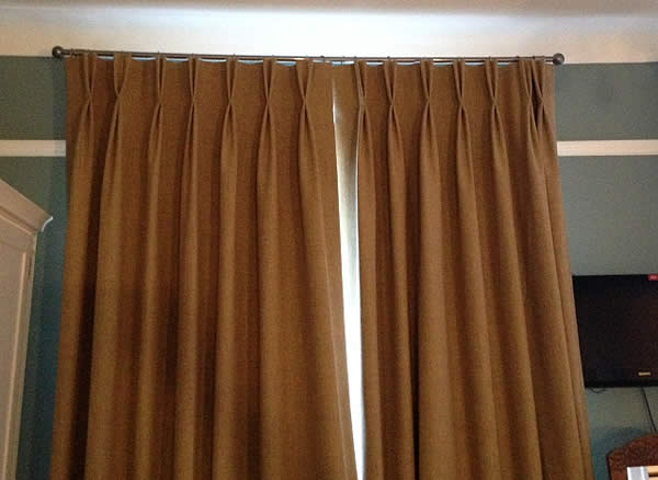Twin pleat Anais Lichen curtains hung on poles.